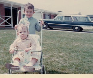 Giving my brother Marty a ride, in front of our Ford station wagon with the hole in the floor.