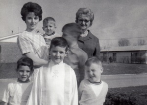 My First Communion photo, with Mom and Grandma in back, David in Mom's arms, Marty to my right, Ken to my left, and Bill over my shoulder.