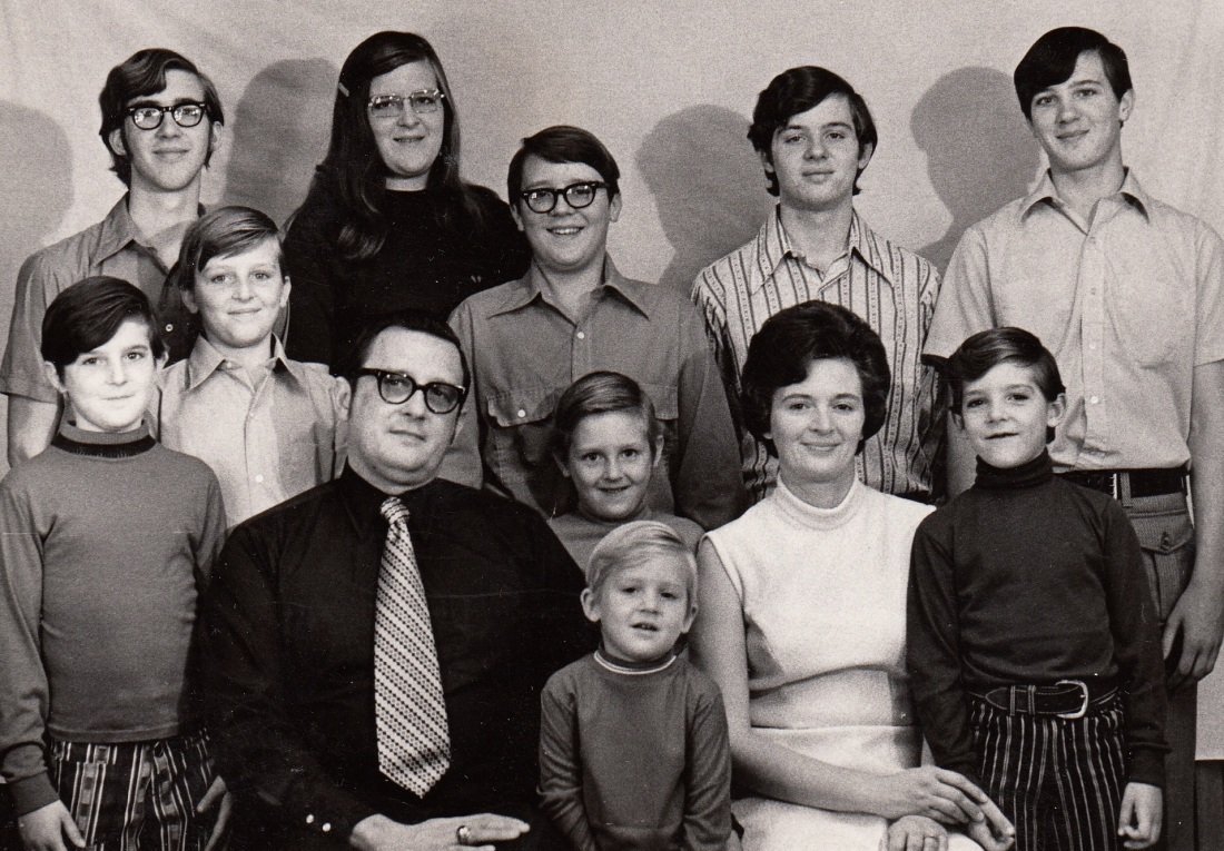 1971 Durbin family portait: Mike, Steve, Bill, Dad, Barb, Ed, Ken, Dave, Mom, Dan, Marty, Bob. On the wall behind us is a bedsheet tacked to the wall.