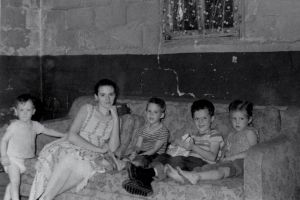 Mom in the basement on Ridge Avenue with kids (L to R), Ed, Steve, Dan and Barb.